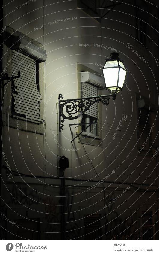 Bei der Laterne Straßenbeleuchtung Menschenleer Haus Mauer Wand Fassade Fenster Rollladen alt leuchten hell Farbfoto Außenaufnahme Textfreiraum unten Nacht
