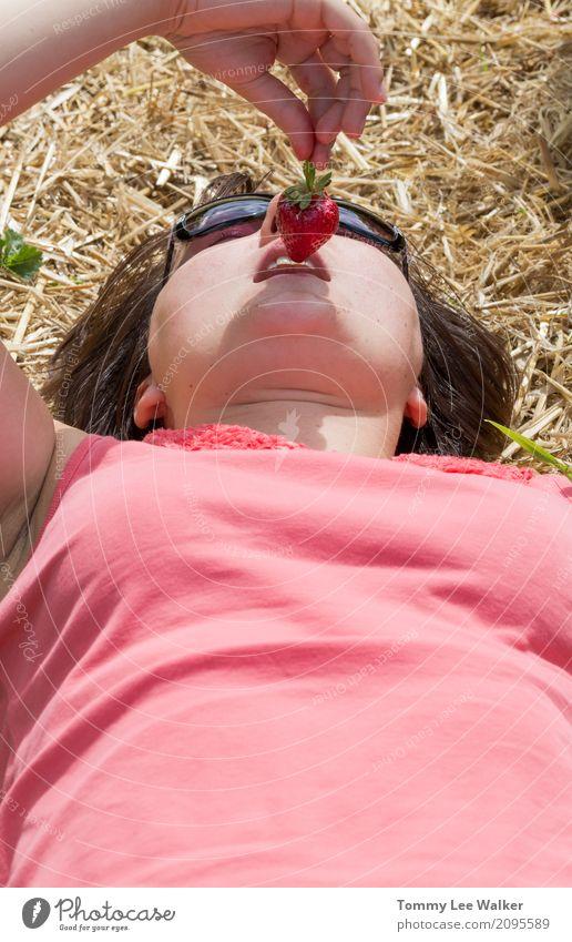 Junge Frau, die mit Erdbeere verlockend ist Lifestyle Freude Leben Erholung ruhig Spielen Freiheit Sommer Sonne Jugendliche Natur Liebe liegen rosa Idee