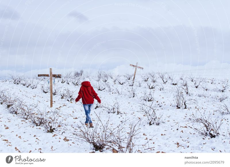 Jemand, der in ein schneebedecktes Feld mit Kreuzen geht Mensch androgyn Jugendliche 1 18-30 Jahre Erwachsene Umwelt Natur Landschaft Himmel Wolken Winter Klima