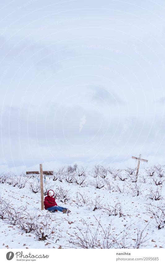 Eine Person, die auf einem Kreuz auf einem schneebedeckten Gebiet sich lehnt Mensch feminin Junge Frau Jugendliche 1 18-30 Jahre Erwachsene Umwelt Natur