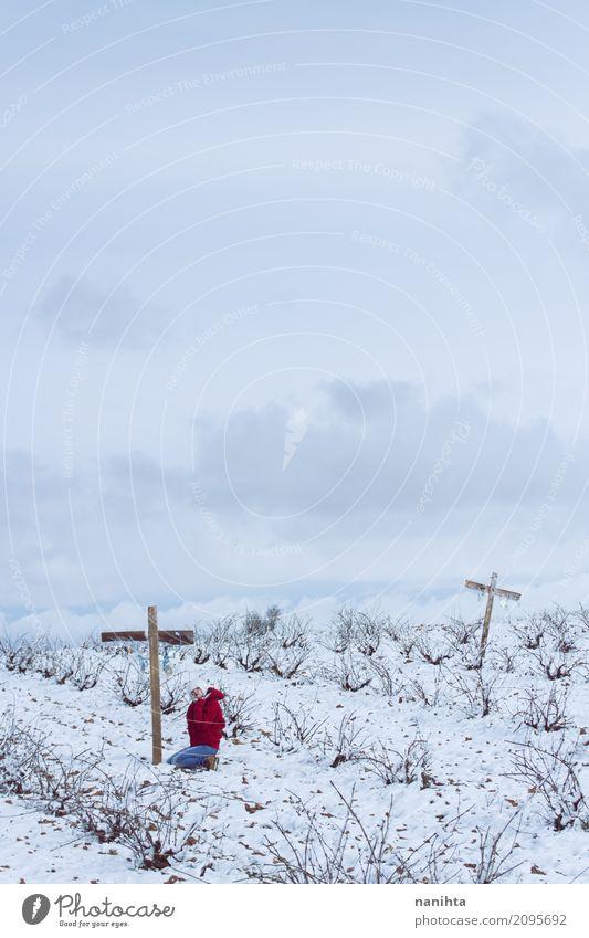 Junge Frau, die in einem Friedhof am Winter betet Mensch Himmel Natur Jugendliche blau weiß Landschaft rot Wolken 18-30 Jahre Erwachsene Religion & Glaube kalt