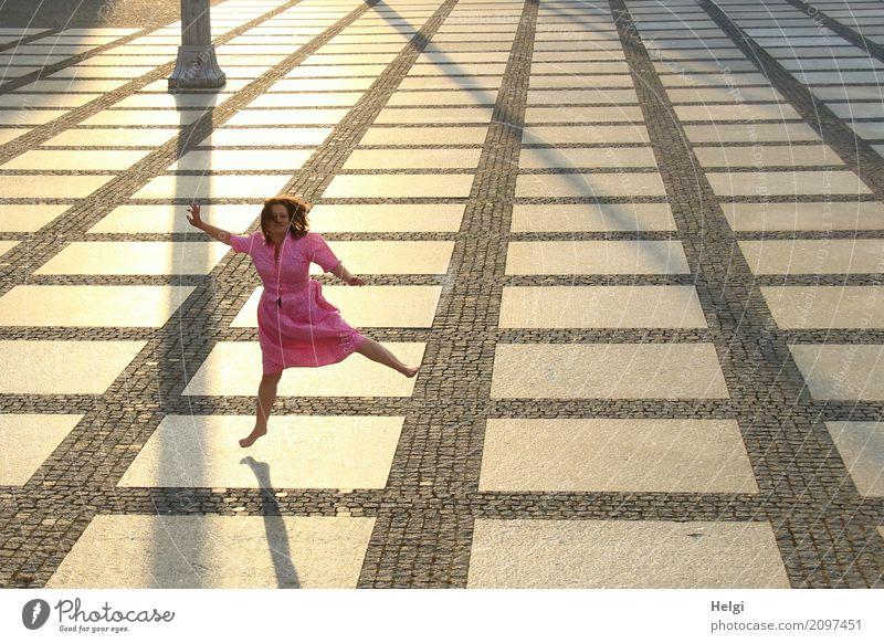 Frau mit langen brünetten Haaren und rosa Kleid hüpft barfuß auf einem großen gepflasterten Platz im Gegenlicht Mensch feminin Erwachsene 1 45-60 Jahre Chemnitz