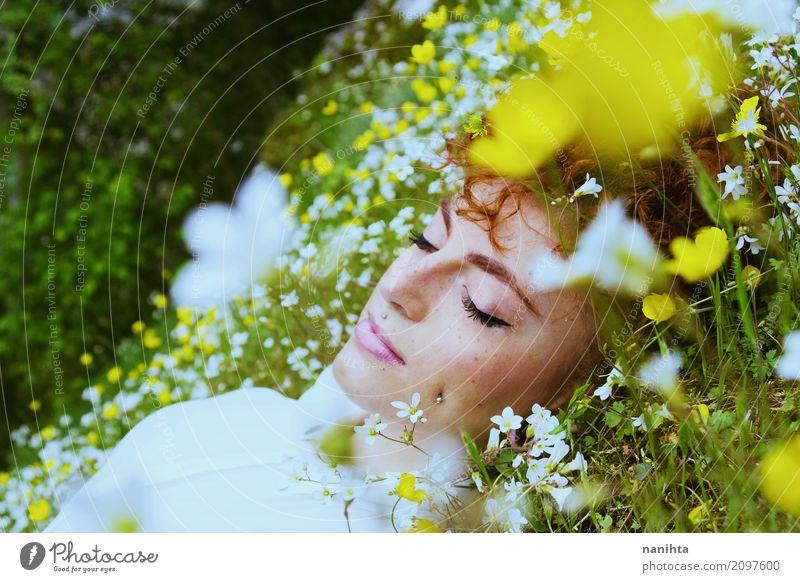Junge Frau, die auf einem Gebiet der Blumen schläft Lifestyle Freude Gesicht Sommersprossen Wellness Wohlgefühl Sinnesorgane Erholung Meditation Duft