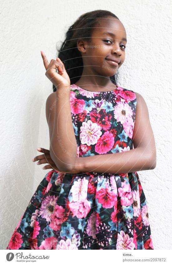 Gloria feminin Mädchen 1 Mensch Mauer Wand Kleid schwarzhaarig langhaarig beobachten festhalten Lächeln Blick Freundlichkeit Fröhlichkeit schön Lebensfreude