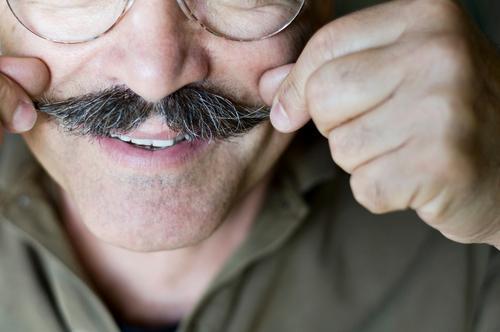 Best Ager zwirbelt seinen Bart Haare & Frisuren Gesicht Leben maskulin Mann Erwachsene Senior Nase Zähne Finger 1 Mensch 45-60 Jahre Lächeln authentisch Glück