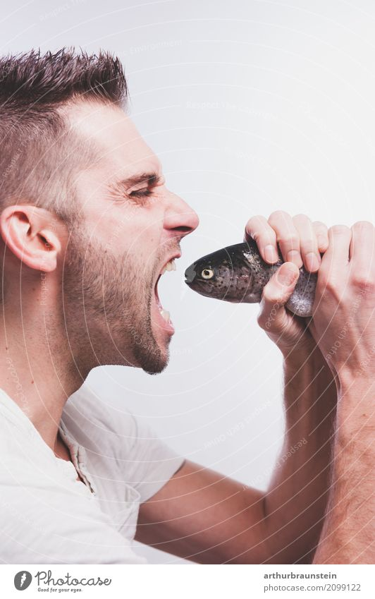 Junger Mann isst frischen Fisch Lebensmittel Forelle Bachforelle Ernährung Essen Bioprodukte Slowfood kaufen Gesunde Ernährung Freizeit & Hobby Angeln Koch