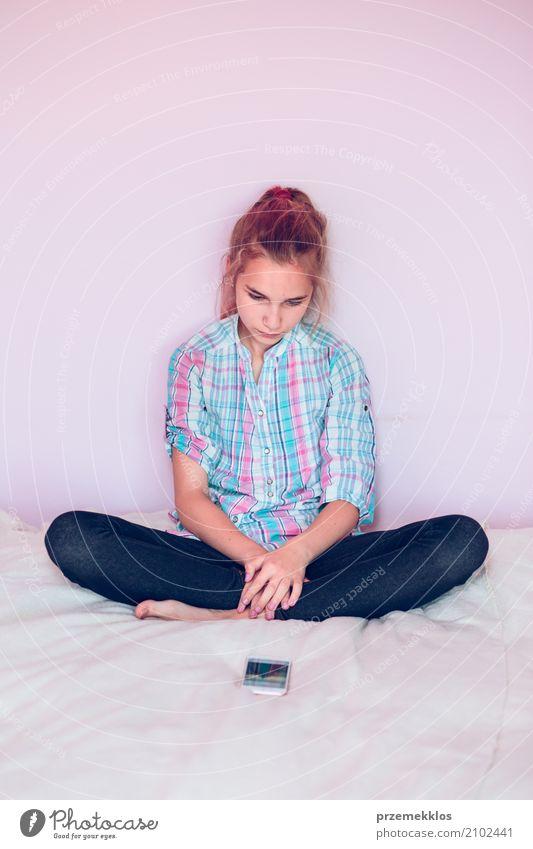 Junges Mädchen, das Handy beim Sitzen auf Bett betrachtet Lifestyle Schlafzimmer Kind Telefon PDA Technik & Technologie Mensch Jugendliche 1 13-18 Jahre modern