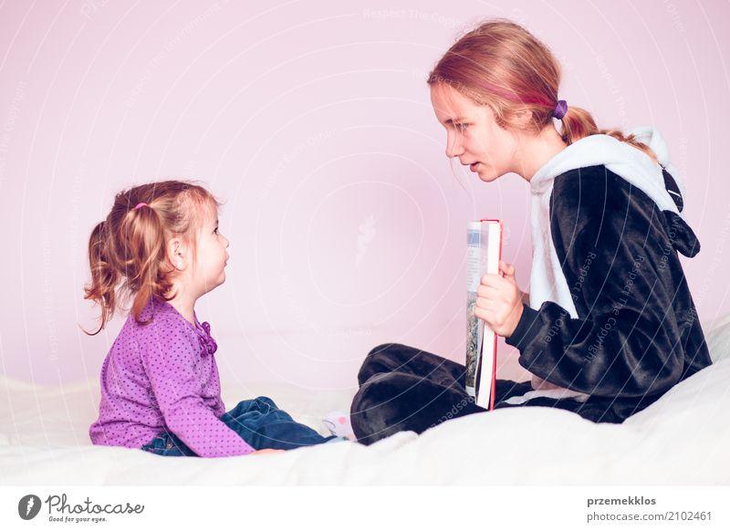 Mädchen, welches die Bilder in einem Buch ihre jüngere Schwester zeigt Lifestyle Bett Kind sprechen Kleinkind 2 Mensch 1-3 Jahre 13-18 Jahre Jugendliche sitzen