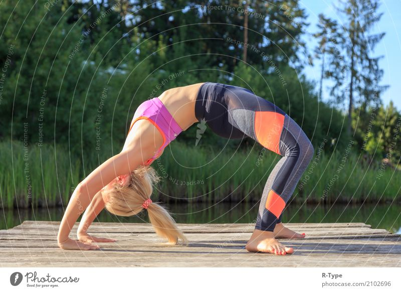 A sporty woman doing yoga and stretching exercises Lifestyle Wellness Leben harmonisch Sport Yoga Mensch Frau Erwachsene Natur Park Mode blond Fitness Aerobics