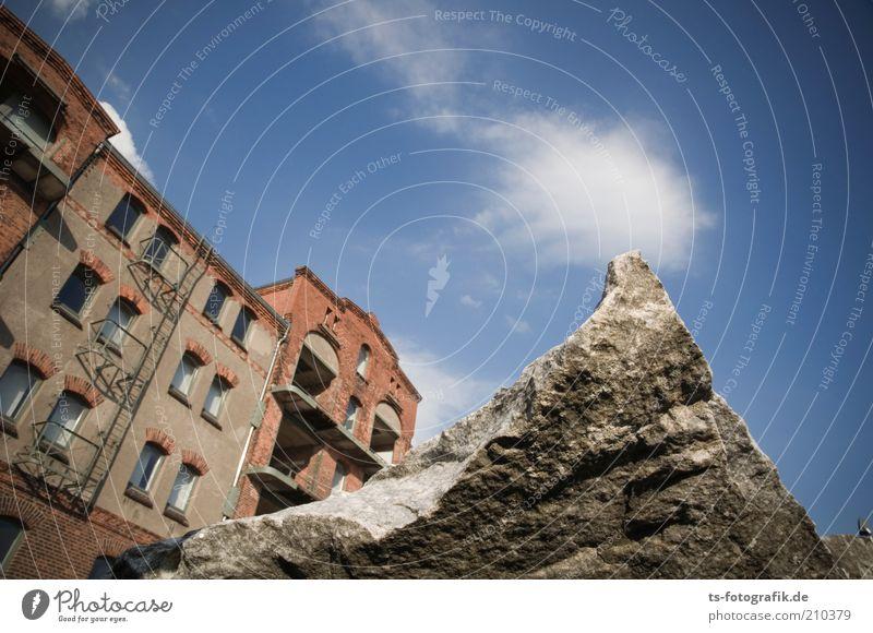 Flachlandtiroler Himmel Wolken Hügel Felsen Haus Industrieanlage Fabrik Ruine Hafen Bauwerk Gebäude Speicher Mauer Wand Fassade Fenster Stein Spitze Geröll