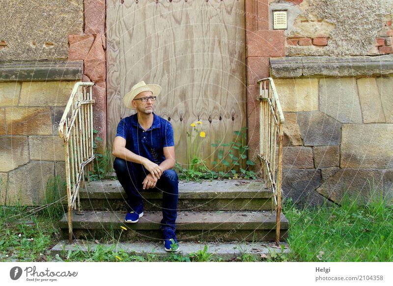 Mann mit Bart, Brille und Sonnenhut sitzt lässig auf einer Treppe vor einem maroden Gebäude Mensch maskulin Erwachsene Männlicher Senior 1 45-60 Jahre Pflanze