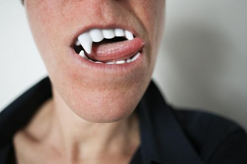 Nahaufnahme eines weiblichen Munds mit Vampirzähnen und Zunge Karneval Halloween Zähne 1 Mensch genießen bedrohlich Begierde Durst gruselig falsch