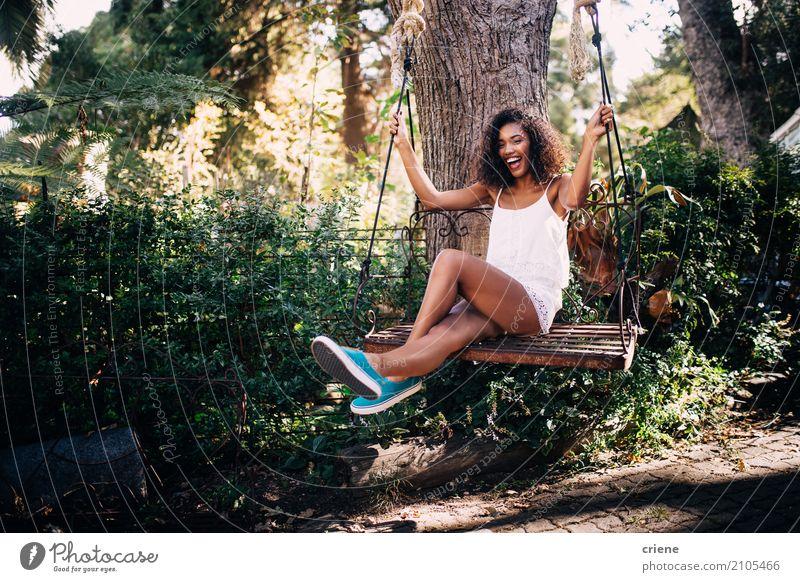 Afrikanerin, die auf Schwingen im Garten im Sommer sitzt Lifestyle Freude Glück Freizeit & Hobby Sommerurlaub Sonne Mensch feminin Junge Frau Jugendliche 1