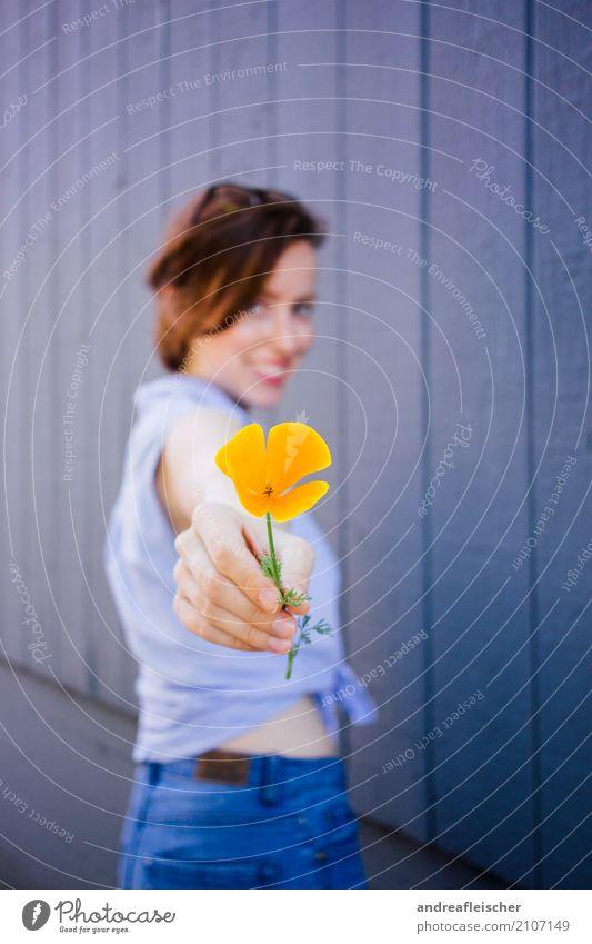 Junge Frau mit orangfarbener Blume in der Hand vor Holzwand Lifestyle elegant Stil Freude schön Gesundheit Wellness Wohlgefühl Zufriedenheit