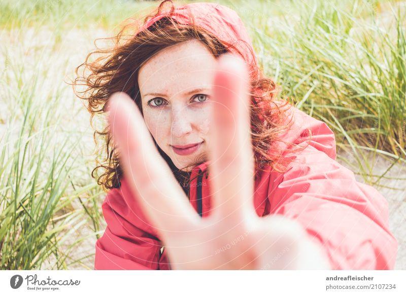 Junge Frau mit Windjacke sitzt in der Düne am Strand und zeigt das Peacezeichen Lifestyle Ferien & Urlaub & Reisen Tourismus Ausflug Ferne Freiheit Sommer