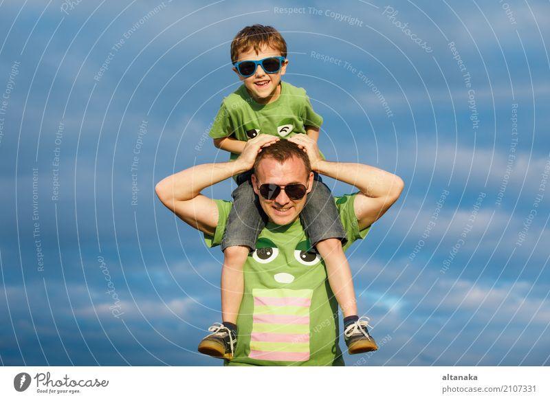 Vater und Sohn, die auf die Straße zur Tageszeit gehen. Mensch Kind Natur Ferien & Urlaub & Reisen Mann Sommer Sonne Freude Strand Erwachsene Lifestyle Sport
