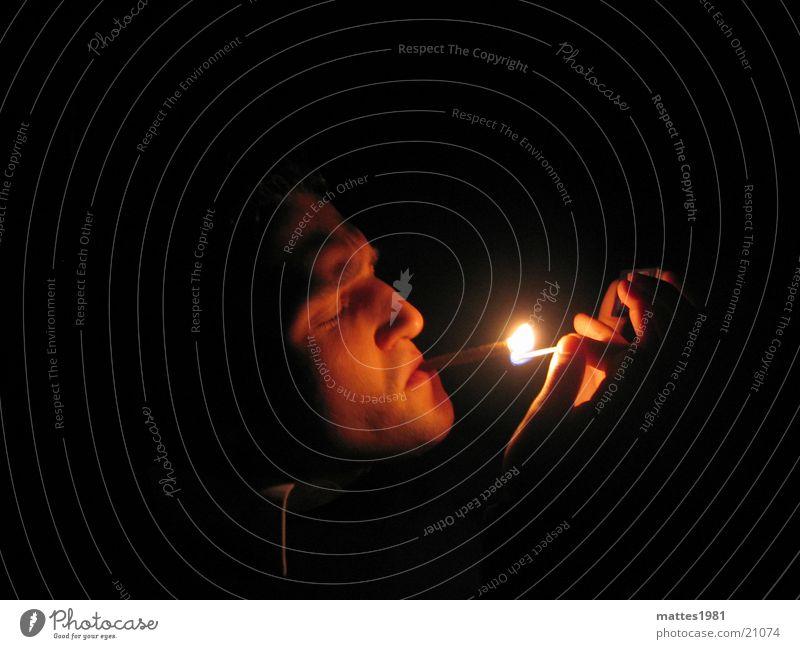rauchender Kopf Mann ruhig Wärme Rauchen genießen Momentaufnahme Streichholz anzünden Männergesicht inhalieren gesundheitsschädlich Vor dunklem Hintergrund
