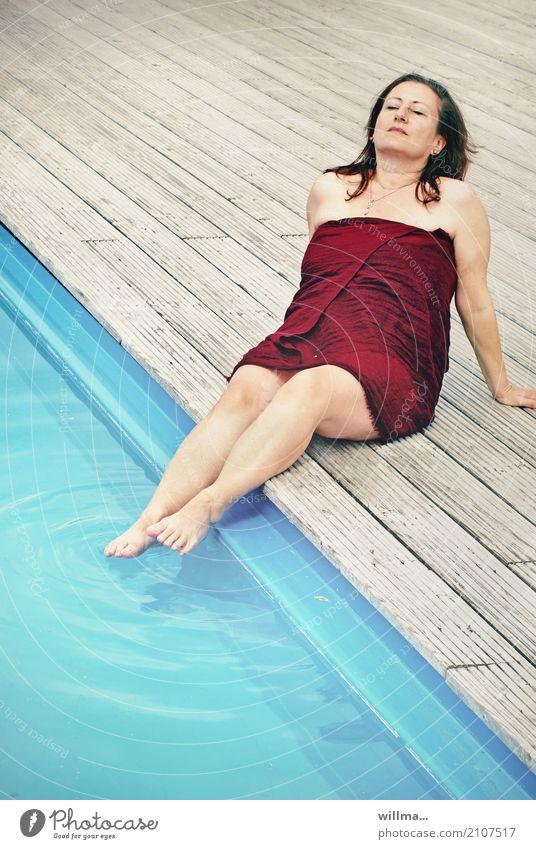 reife brünette frau in badetuch gewickelt sonnt sich am pool mit den füßen im wasser | lebenselixier wasser Lifestyle Wohlgefühl Zufriedenheit Erholung ruhig