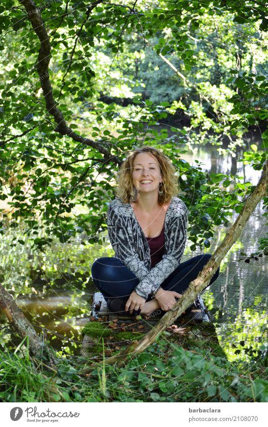 Lebenselixier l Natur feminin Frau Erwachsene 1 Mensch Landschaft Urelemente Wasser Sonne Pflanze Sträucher Seeufer Teich lachen sitzen Fröhlichkeit Gefühle