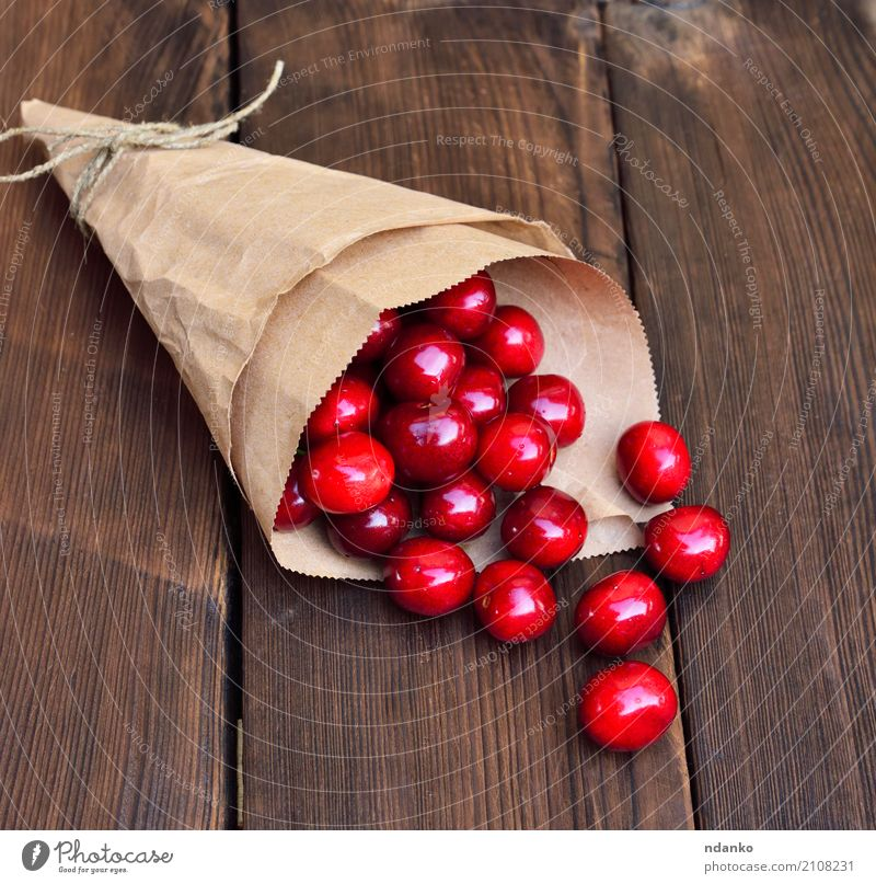 Reife rote Kirsche in einer Papiertüte Frucht Dessert Essen Vegetarische Ernährung Saft Sommer Tisch Natur Holz frisch natürlich oben retro saftig Hintergrund