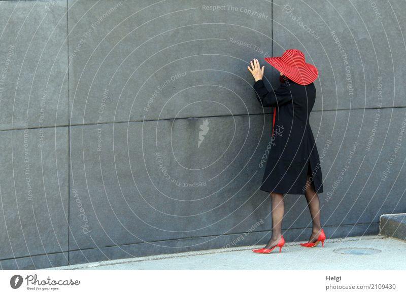 Rückansicht einer elegant gekleideten Dame mit schwarzem Mantel, rotem Hut und roten Pumps vor grauer Wand Mensch feminin Frau Erwachsene Weiblicher Senior 1