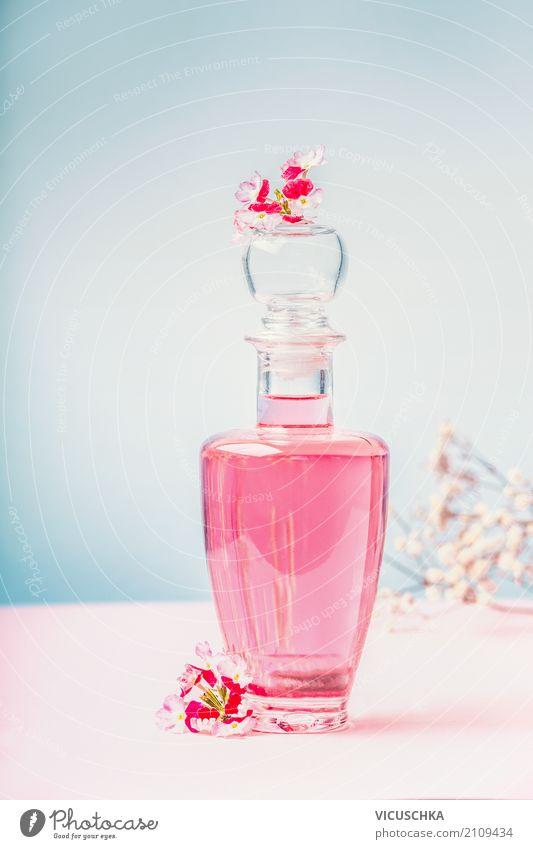 Flasche mit Lotion oder Parfüm mit rosa Blüten Lifestyle Stil Design schön Körperpflege Kosmetik Parfum Wellness Spa Massage Natur Blume Blatt aromatisch