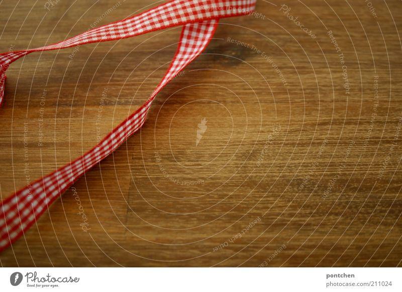 Ein rot-weiß kariertes Geschenkband liegt auf einem Holztisch. Weihnachten, verpacken, zubinden Stil Design Basteln einrichten Dekoration & Verzierung Kitsch