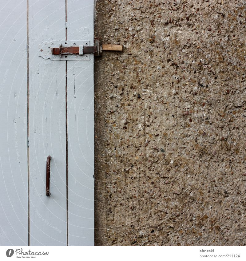 Schuppen Hütte Gebäude Scheune Mauer Wand Fassade Tür grau Schloss Griff Gedeckte Farben Außenaufnahme Textfreiraum rechts Detailaufnahme Holztür Menschenleer