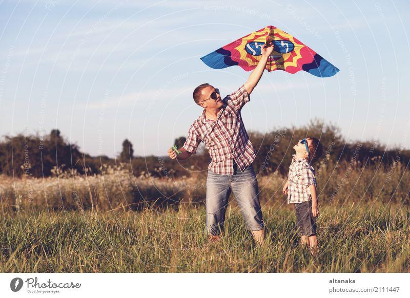 Vater und Sohn, die im Park zur Sonnenuntergangzeit spielen. Mensch Kind Natur Ferien & Urlaub & Reisen Mann Sommer Freude Erwachsene Straße Lifestyle Sport
