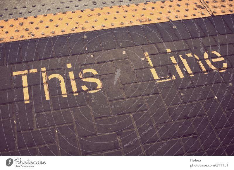 This Line! alt gelb Linie dreckig Verkehr Eisenbahn Boden Buchstaben Zeichen U-Bahn Warnhinweis Bahnhof Wort Pflastersteine Vorsicht