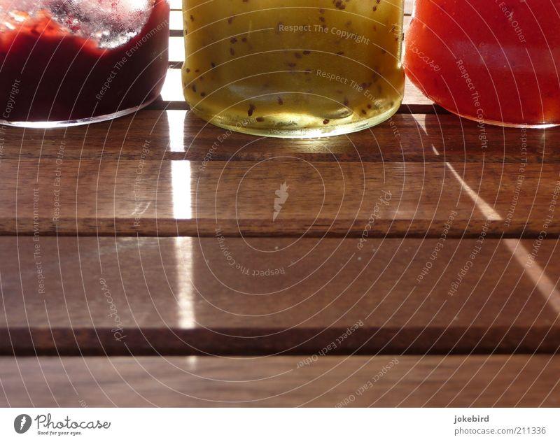 Frühstückskombo Lebensmittel Marmelade Ernährung Tisch Holz Glas braun grün rot konservieren konserviert Vorrat Gelatine süß Marmeladenglas Farbfoto