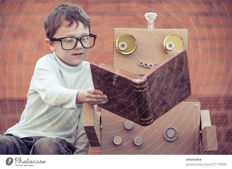 Ein kleiner Junge liest im Freien einem Roboter aus Pappkartons vor. Konzept von Wissenschaft und Bildung. Lifestyle Freude Glück schön Erholung