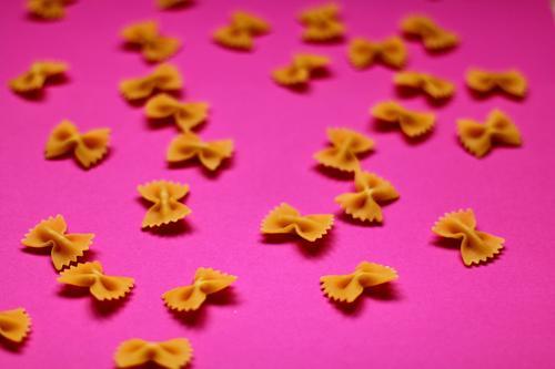 Teigwaren beugt auf rosa backgriund Lebensmittel Backwaren Ernährung Essen Mittagessen Bioprodukte Vegetarische Ernährung Diät Fasten Fingerfood