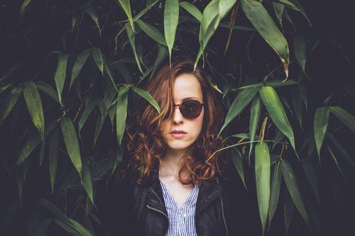 Junge Frau mit Sonnenbrille steht im Bambusbusch Lifestyle elegant Stil Haare & Frisuren Ferien & Urlaub & Reisen Ausflug feminin Jugendliche 1 Mensch
