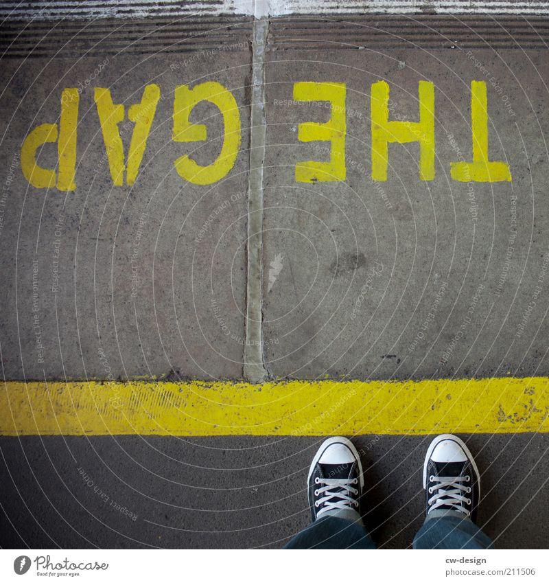 ONE STEP BEYOND Mensch gelb Fuß Beine warten stehen Schriftzeichen Hinweisschild Chucks Am Rand Warnhinweis Lücke Bahnsteig Zone Begrenzung Unfallgefahr