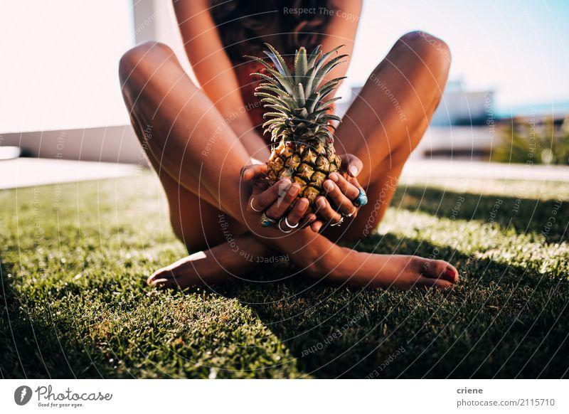 Frau im Badeanzug, der auf dem Gras hält Ananas sitzt Lebensmittel Frucht Ernährung Lifestyle Freude schön Freizeit & Hobby Ferien & Urlaub & Reisen Sommer