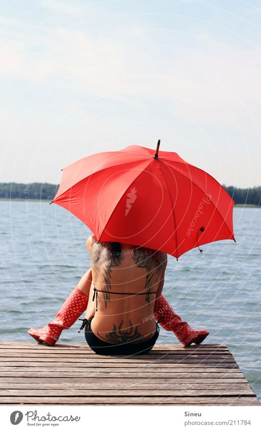 Warten auf Godot Frau Erwachsene Rücken Natur Wasser Himmel Sommer Schönes Wetter Seeufer Bikini Gummistiefel Regenschirm sitzen warten frech frei rot Hoffnung