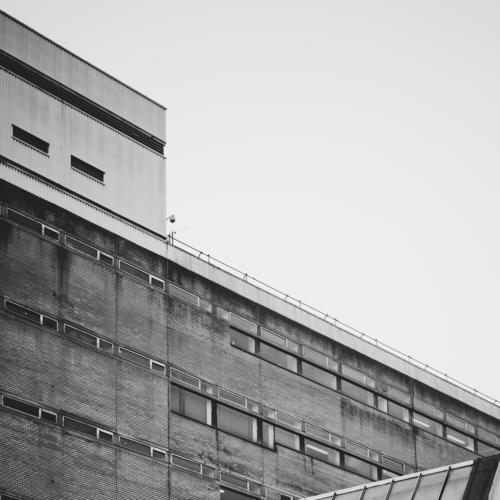 Glasgow im Nebel I Stadt Haus Fenster Architektur Wand Mauer grau Fassade Hochhaus ästhetisch trist Neigung Bauwerk Skyline Stadtzentrum abwärts