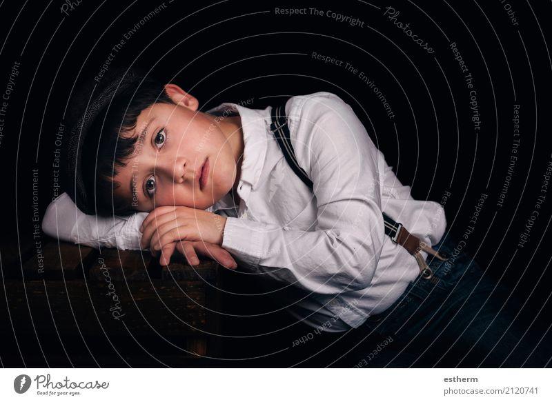 Nachdenklicher Junge auf schwarzem Hintergrund Lifestyle Mensch maskulin Kind Kleinkind Kindheit 1 3-8 Jahre Mütze Denken liegen schlafen Traurigkeit trist