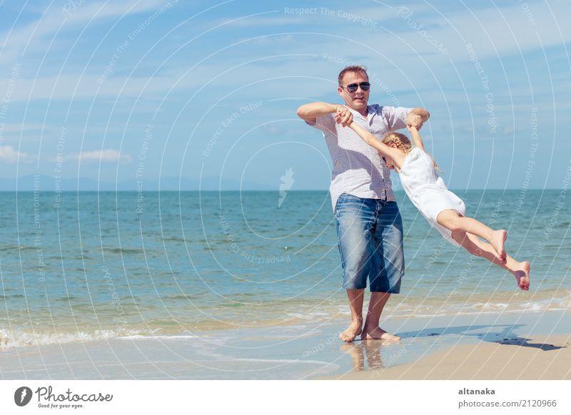 Vater und Tochter, die am Strand zur Tageszeit spielen. Kind Frau Natur Ferien & Urlaub & Reisen Sommer Sonne Hand Meer Erholung Freude Erwachsene Leben