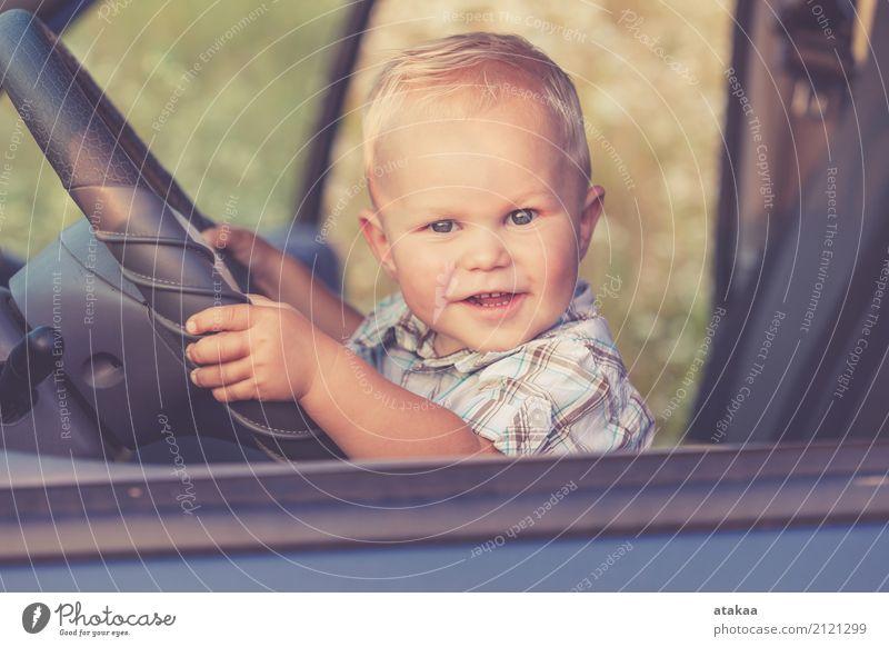 Ein kleiner Junge sitzt im Auto und schaut zur Tageszeit aus dem Autofenster. Konzept der glücklichen Reise. Lifestyle Freude Glück schön Leben Freizeit & Hobby