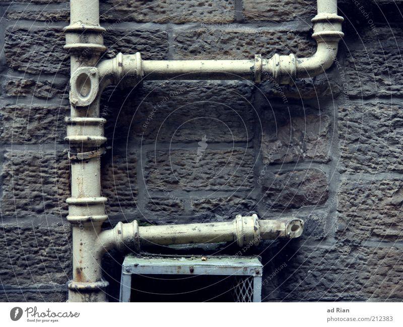 überfluss Mauer Wand Dachrinne Ordnungsliebe Farbfoto Außenaufnahme Detailaufnahme Menschenleer Steinmauer Rohrleitung Eisenrohr Leitung Verbindung