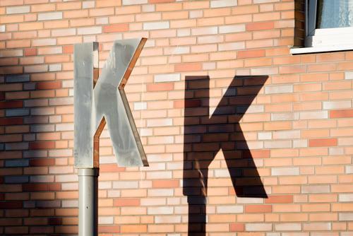 K K Mauer Wand Schriftzeichen Stadt braun schwarz silber Buchstaben Licht & Schatten Pylon Hausmauer Außenaufnahme Detailaufnahme Menschenleer Tag