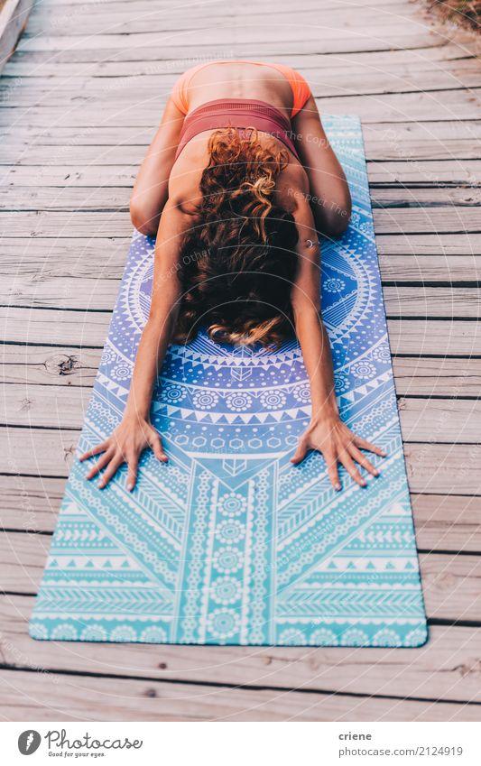 Junge Frau, die Yoga tut und Übung auf Yogamatte ausdehnt Lifestyle Wellness Erholung Freizeit & Hobby Sport Fitness Sport-Training Mensch feminin Jugendliche