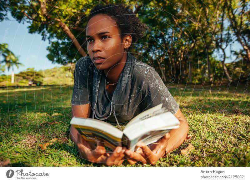 Junge afroamerikanische Frau beim Lesen eines Buches, das auf dem grünen Rasen liegt. Lifestyle feminin Junge Frau Jugendliche 1 Mensch 18-30 Jahre Erwachsene