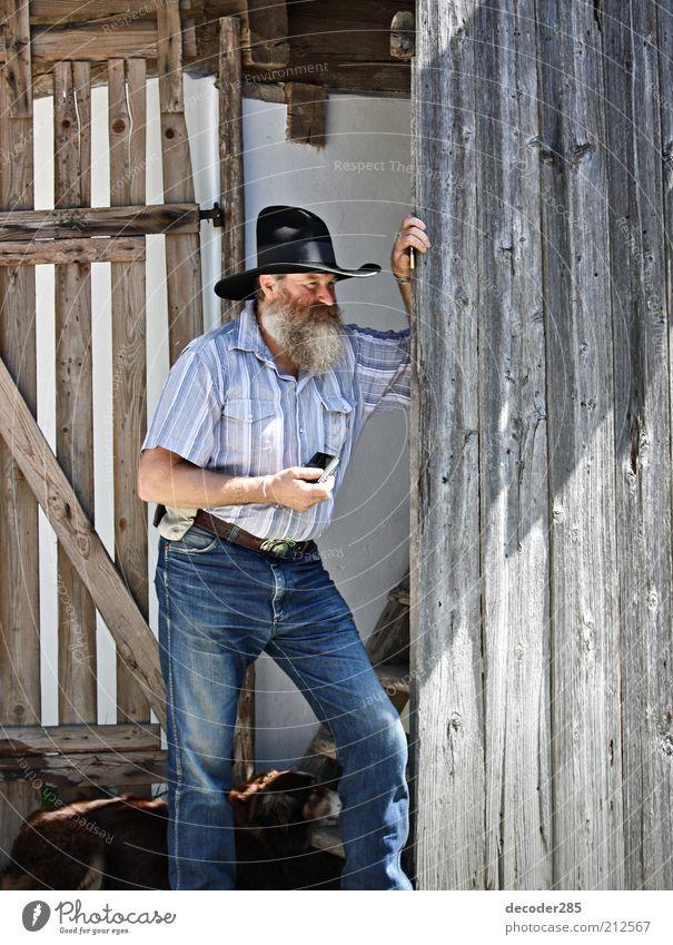 Fröschl Sepp – Cowboy Mensch Mann alt Sommer Erholung Wand Holz Hund Mauer Erwachsene maskulin Jeanshose stehen authentisch Fotokamera Hose
