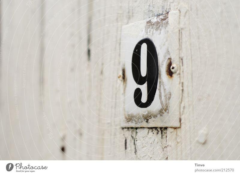Hausnummer 9 auf weißer Holzwand alt schwarz Schilder & Markierungen Wandel & Veränderung Ziffern & Zahlen Vergänglichkeit abblättern verwittert Tür angemalt