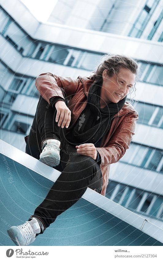 Jugendliche in Lederjacke sitzt lässig auf einer Mauer in der Stadt sitzen Lifestyle Mensch Junge Frau Erwachsene Leben Hochhaus Rastalocken Lächeln blau