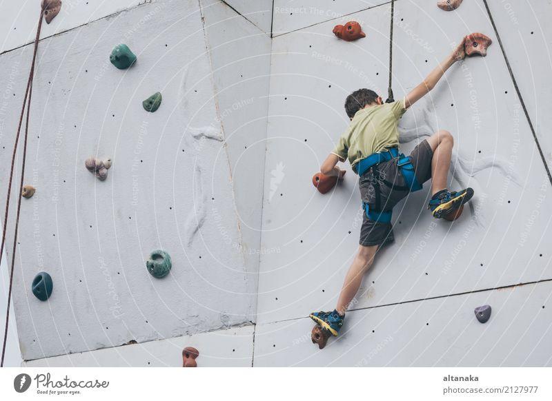 kleiner Junge, der eine Felsenwand im Freien klettert. Freude Freizeit & Hobby Spielen Ferien & Urlaub & Reisen Abenteuer Camping Entertainment Sport Klettern