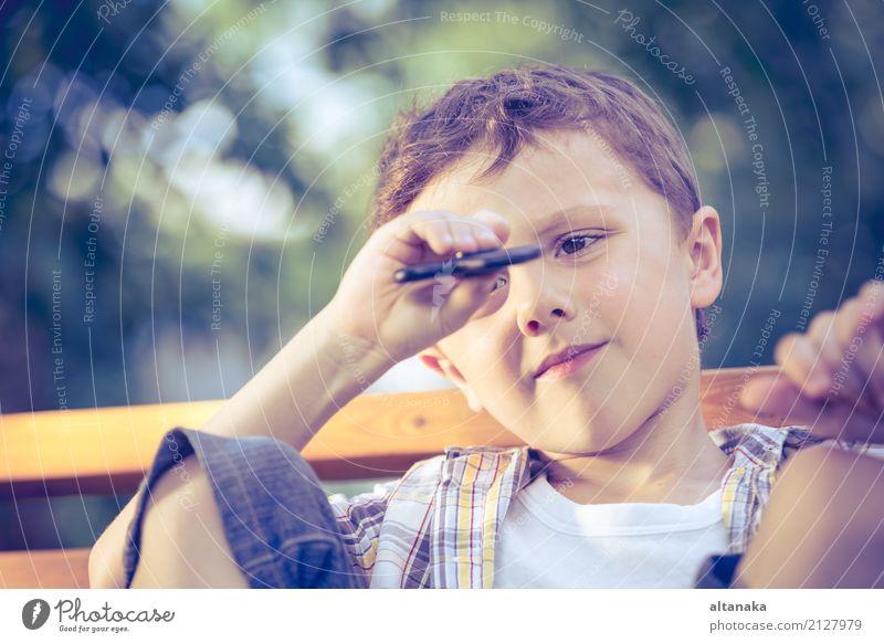 Glücklicher kleiner Junge, der im Park zur Tageszeit spielt. Mensch Kind Mann Sommer schön Hand Erholung Freude Gesicht Erwachsene Lifestyle Gefühle Spielen